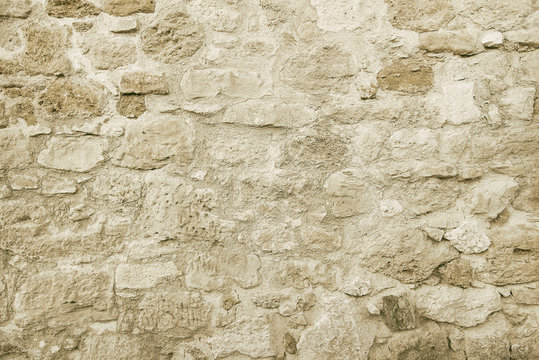 Old beige stone wall background texture