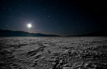 The moon sets in Death Valley NP from Badwater salt flats, lowest point in the US.