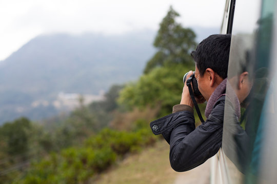 Tourist taking pictures from car