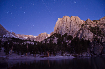 A meteor streaks through the pre-dawn light over Lone Pine Lake.