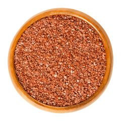 Hawaiian red sea salt in wooden bowl. Alaea salt, unrefined coarse grain, mixed with iron oxide rich volcanic clay. Characteristic brick red color. Seasoning. Food photo closeup from above over white.