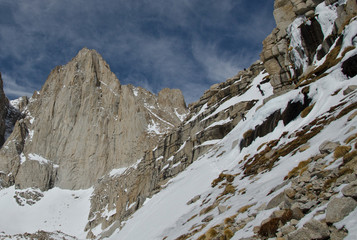 Three hikers climbing Mount Whitney as they approach Iceberg Lake on the Mountaineers Route.