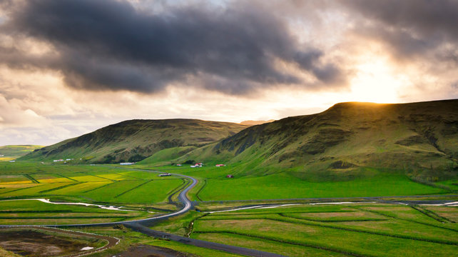 Sunset along the ring road in Southern Iceland overlooking green farm fields and hills.