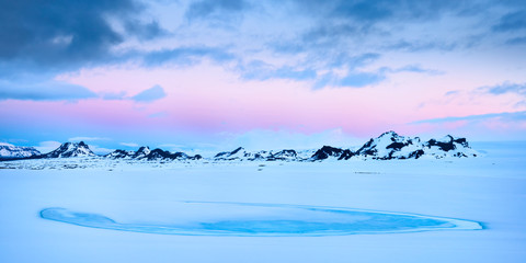 Dawn breaks over the mountains on the edge of the Langjokull glacier in the highlands of Iceland.