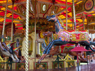 Close up of colorful carousel horses in the park