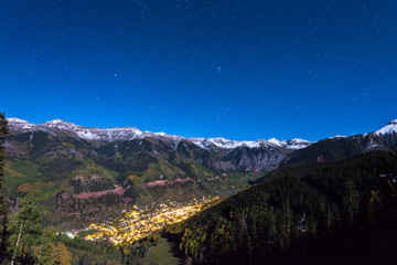 The glowing lights of the town of Telluride Colorado underneath the stars.
