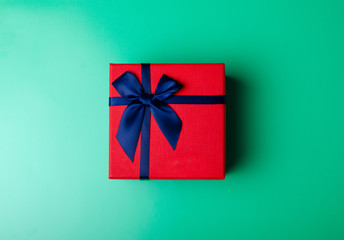 Red box gift with blue ribbon on green background, top view fashion flat lay