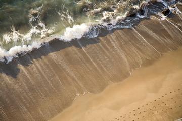 Waves crashing on beach below the Golden Gate Bridge. San Francisco, California.