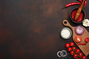 Set of products on cutting board from cherry tomatoes, rosemary, garlic, red pepper, onion, salt and spice mortar on rusty brown background