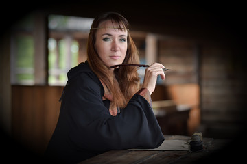 A woman in a medieval cloak sits with a pen
