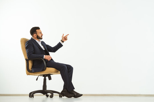 The businessman sitting on an office chair on the white background and gesturing