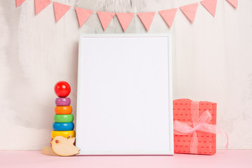 Festive mood, children's garland with a white empty frame for design, and toys with gift layout. Baby shower