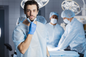 Multi-ethnic medical group with a good-looking surgeon wearing sterile latex gloves and uniform, confidently looking at camera in a hospital operation room