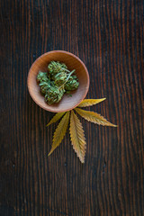 Marijuana in wooden bowl on table with leaves