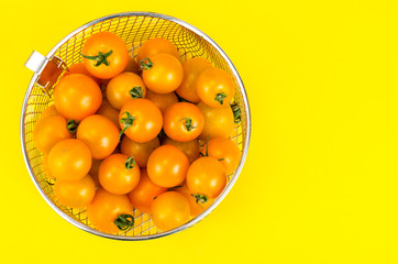 Yellow ripe small tomatoes in metal basket