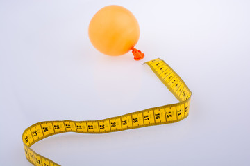 Yellow color measuring tape and a balloon