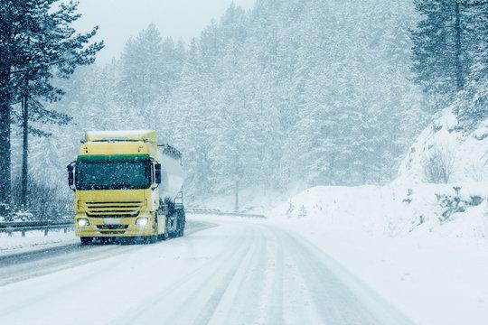 Traffic truck on winter road in snow blizzard