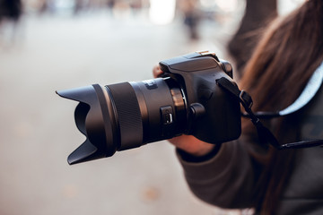 Black SLR camera in the hands of a girl