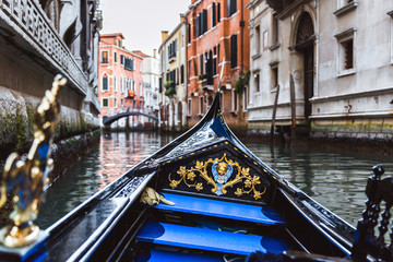 Traditional gondola on narrow canal in Venice, Italy