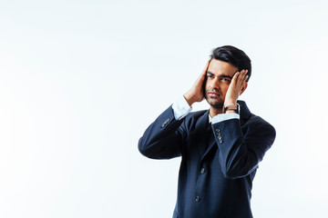 Portrait of a cool businessman holding his head in disbelief or in pain, isolated on white background..