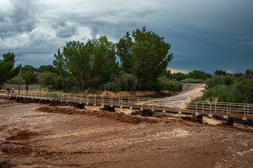 Flash flood running running over road in rural desert town