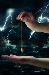 Close up of woman's hand holding a pendulum in motion over her palm. Thunderstorm at night in background.