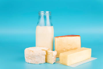Various fresh dairy products isolated on blue background. Cheese, milk and butter.