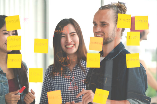Hipster attractive young caucasian man and young asian chinese girl talk and brainstorming together at glass wall sharing business ideas project plans with post it sticky note. Marketing plan concept.