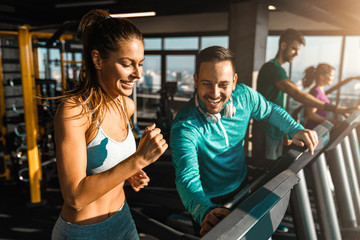 Happy athletic couple communicating while jogging on treadmills in a health club