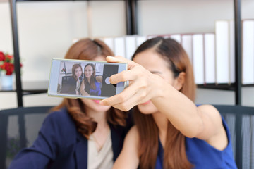 Cheerful young Asian business women taking a picture or selfie together in office.