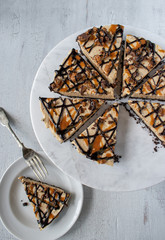 Caramel and chocolate drizzle peanut butter tart pie with slices on white marble flat lay