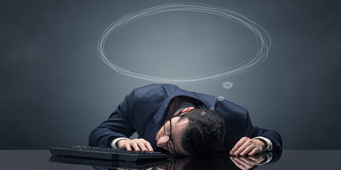 Young businessman sleeping and dreaming at the office