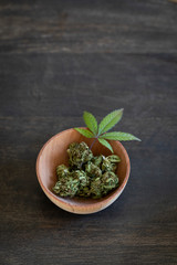 Bowl of dried marijuana and green leaf on wood surface