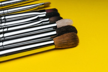 professional set of red makeup brushes on yellow background with copy space close up