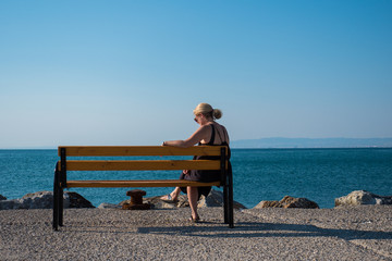 Blond woman sitting on bench on stone dock by the ocean in summer, blue sky