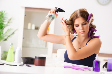 Young woman with hair curlers at barbershop