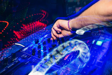 DJ in a booth playing a mixer at a nightclub at a party