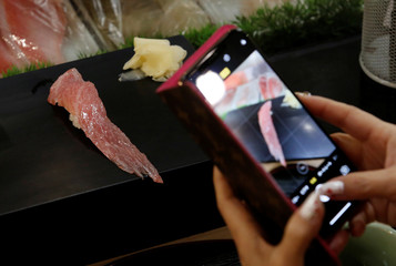 A customer takes pictures of a sushi roll made with meat from a 278kg bluefin tuna, priced with a 333,600,000 yen bid at the Toyosu fish market's first tuna auction this year, at Sushi Zanmai restaurant in Tokyo