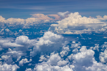 Beautiful view from window of plane flying over clouds. Natural panorama with clouds. White clouds moving above the ground.