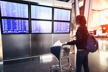 Female passenger at the airport looking at the flight information board Wall mural