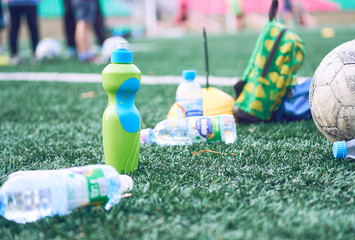 Plastic bottles with blurry soccer training equipment on artificial turf. It is waste from soccer training or football match.
