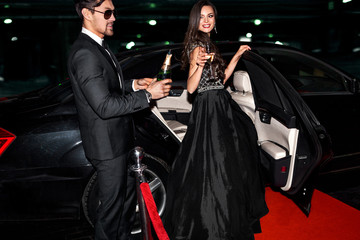 Sexy couple near the car. Hollywood star. Fashionable pair of elegant people at night city street.