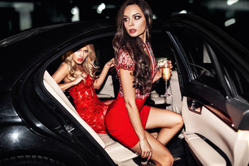 Canvas Prints People Sexy woman couple in the car. Hollywood star. Fashionable pair of elegant people at night city street.