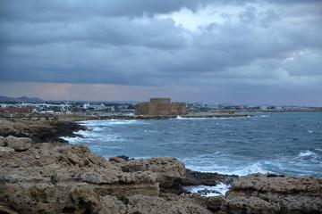 Krajobraz wybrzeża w Pafos, Cypr, skalisty brzeh, lekko wzburzone morze, średniowieczny ufortyfikowany zamek na cyplu, w oddali zabudowa mista, wzgórza