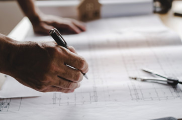 close up of hand professional architect, engineer or interior reviewing blueprint on workplace desk in office center at construction site, contractor, construction, engineering and business concept