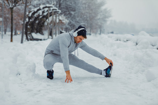 Young man stretching legs on snowy day in the city