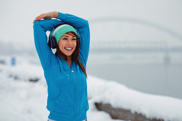 Young woman stretching arms on snowy day in the city