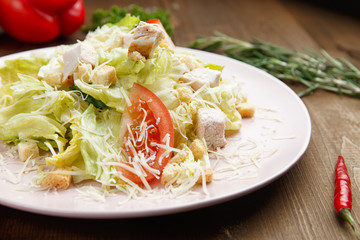 Caesar salad in a plate on a wooden background