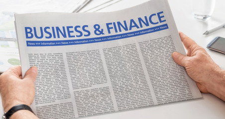Man reading newspaper with the headline Business and Finance