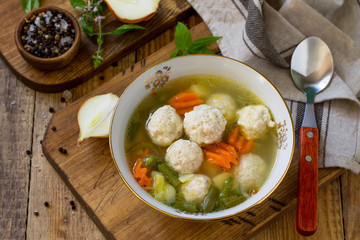 The concept Diet menu. Healthy soup with vegetables and chicken meatballs in a bowl on wooden table in rustic style.